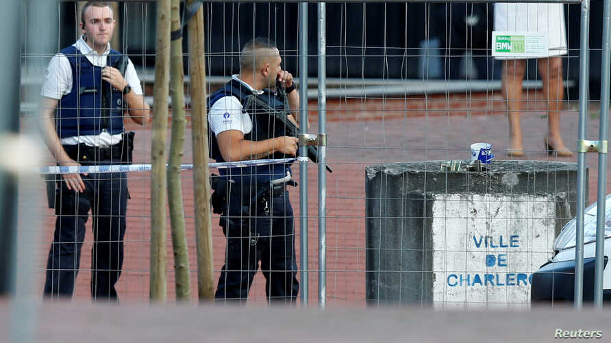 Belgian police officers stand guard outside the main police station after a machete-wielding man injured two female police officers before being shot dead in Charleroi, August 6, 2016.