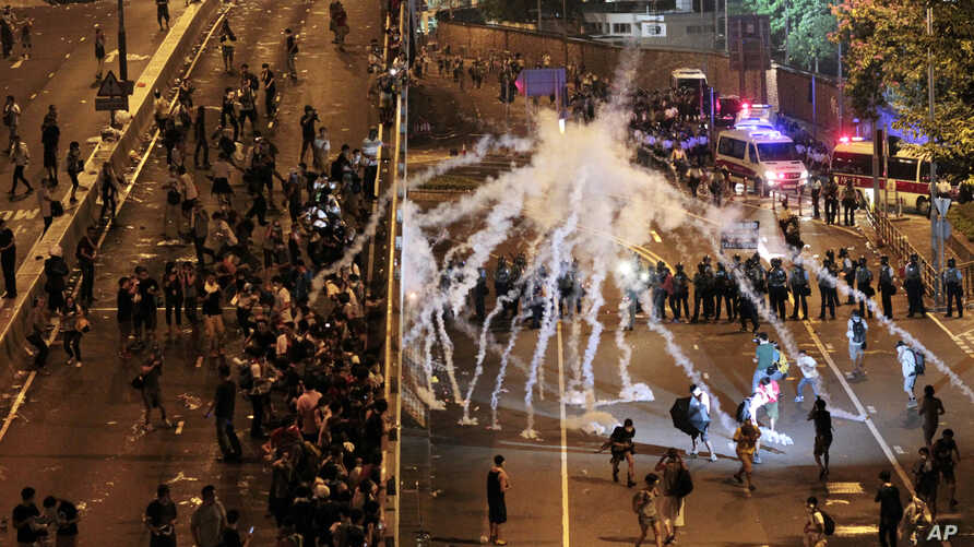 Riot police fire tear gas on student protesters occupying streets surrounding the government headquarters in Hong Kong, early Sept. 29, 2014.