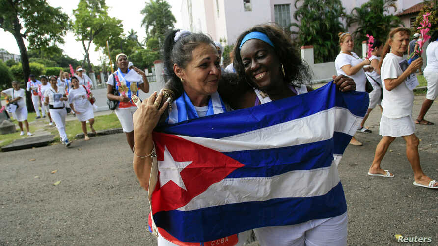 Recently released dissidents Haydee Gallardo (L) and Sonia Garro hold the Cuban national flag during a march in Havana, Jan. 11, 2015.