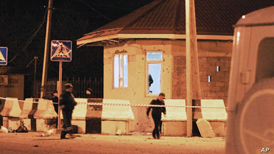 Investigators pass a damaged police check point in the village of Karabudakhkent, 30 kilometers (18 miles) south of the provincial capital, Makhachkala, Russia, March 6, 2012.