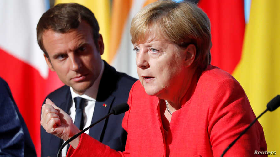 FILE - French President Emmanuel Macron and German Chancellor Angela Merkel attend a news conference following talks on European Union integration, defense and migration at the Elysee Palace in Paris, Aug. 28, 2017.