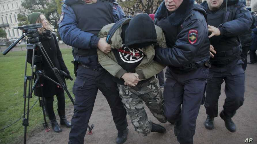 Police officers detain a man during a protest in St.Petersburg, Russia, Nov. 5, 2017.