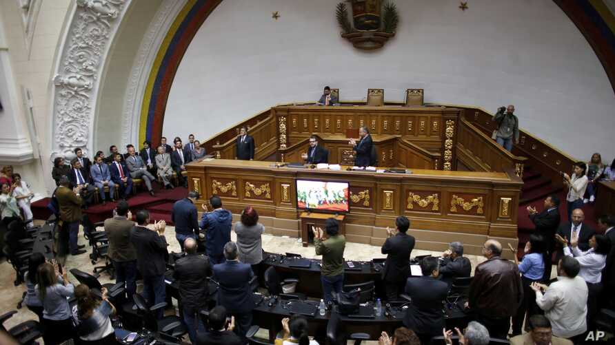 Members of the diplomatic corps, left , listen as lawmakers applaud during a session of Venezuela's National Assembly in Caracas,  Aug. 19, 2017. Venezuela's pro-government constitutional assembly took over the powers of the opposition-led congress F
