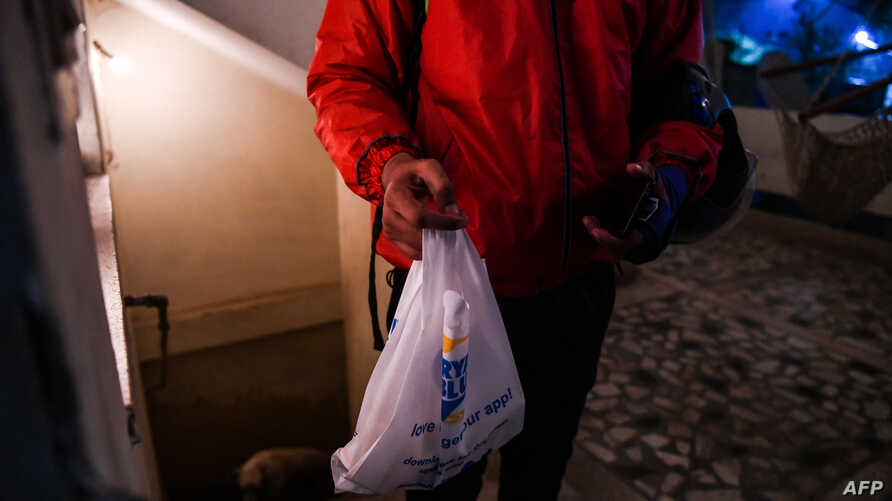 Delivery man Ujjwal Singhal working with the food delivery app Swiggy carries an order to a customer in New Delhi, India, Feb. 6, 2019,.