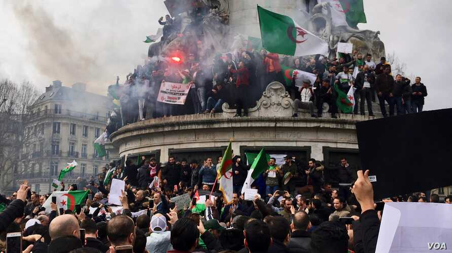 Algerians climbed on the iconic Marianne statue in downtown Paris, France, March 4, 2019.