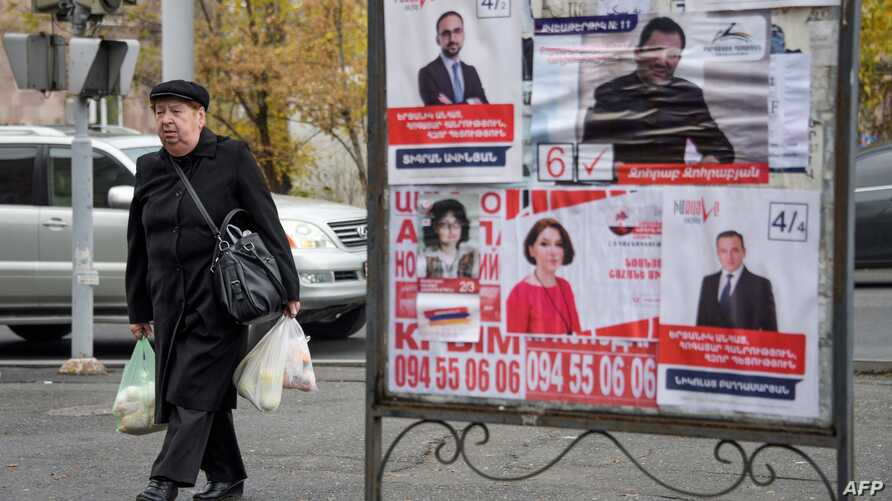 People walk past election posters in Yerevan, Dec. 6, 2018, days before Sunday's early parliamentary elections.