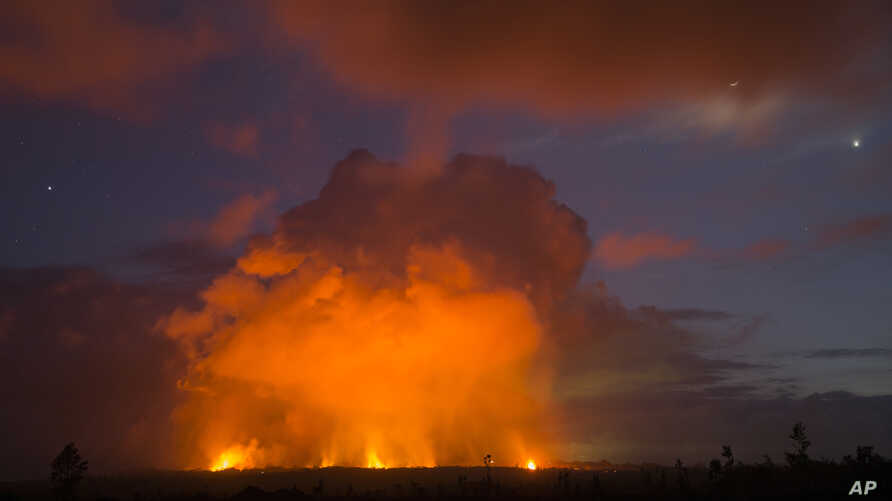 Volcanic activity from the Malama Ki and Leilani Estates neighborhoods glows in the distance from Hwy 137, May 17, 2018, near Pahoa, Hawaii