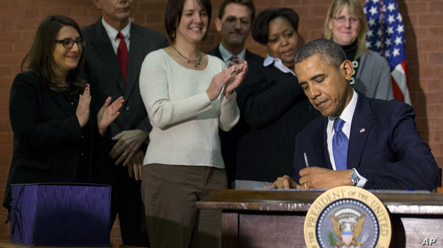 President Barack Obama signs the $1.1-trillion spending bill that funds the federal government through the end of September, at Jackson Place, a conference center near the White House in Washington, Jan. 17, 2014.
