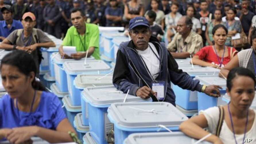 Electoral commission workers stand beside ballot boxes to be sent to villages in Dili, East Timor, March 16, 2012.