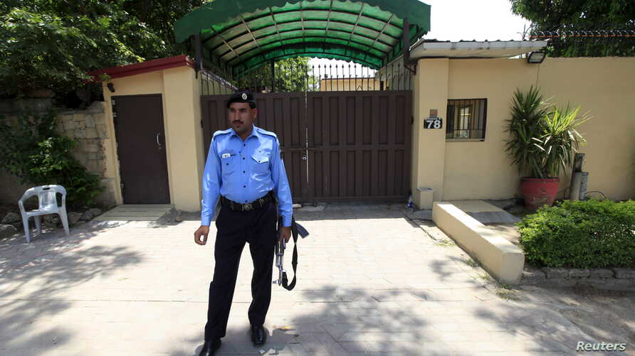 A policeman stands guard outside the Save the Children charity's office in Islamabad, Pakistan, June 12, 2015.