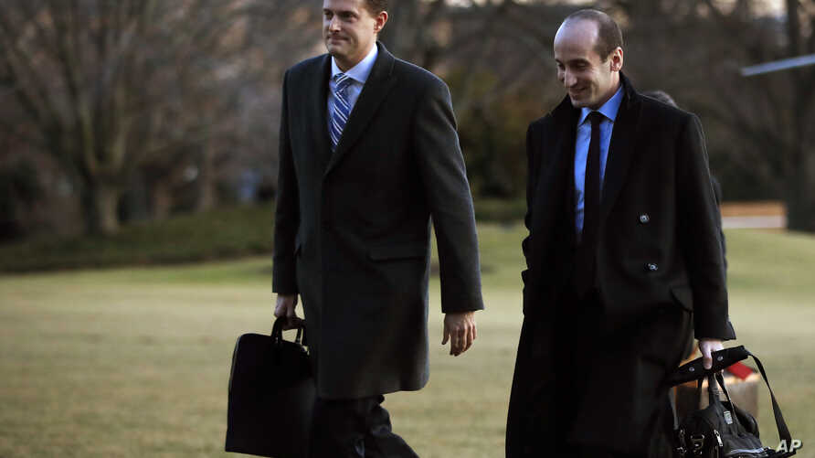 White House staff secretary Rob Porter (L) walks with White House senior adviser Stephen Miller from Marine One across the South Lawn of the White House in Washington, Feb. 5, 2018.