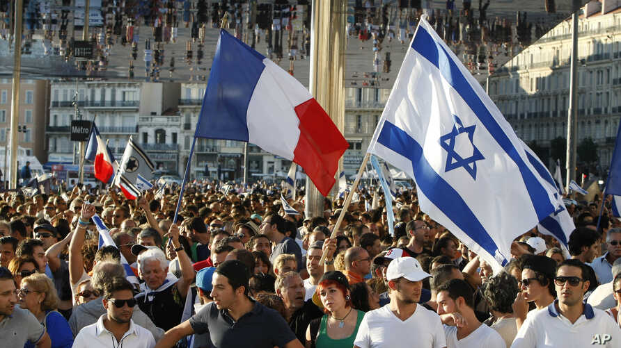 Supporters of Israel's Gaza offensive wave Israeli and French flags at a demonstration in Marseille, France, July 27, 2014. The radical Jewish Defense League, not shown, uses strong-arm tactics to fight anti-Semitism.