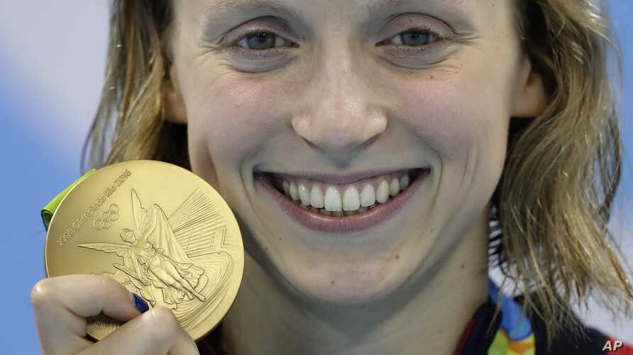 United States' Katie Ledecky shows off her gold medal in the women's 800-meter freestyle medals ceremony during the swimming competitions at the 2016 Summer Olympics, Friday, Aug. 12, 2016, in Rio de Janeiro, Brazil.