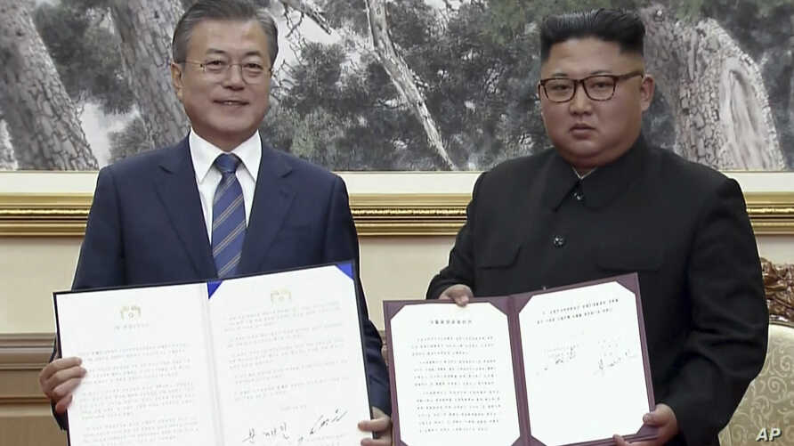 In this image made from video provided by Korea Broadcasting System (KBS),  S. Korean President Moon Jae-in, left, and N. Korean leader Kim Jong Un pose after signing documents in Pyongyang, North Korea Wednesday, Sept. 19, 2018.