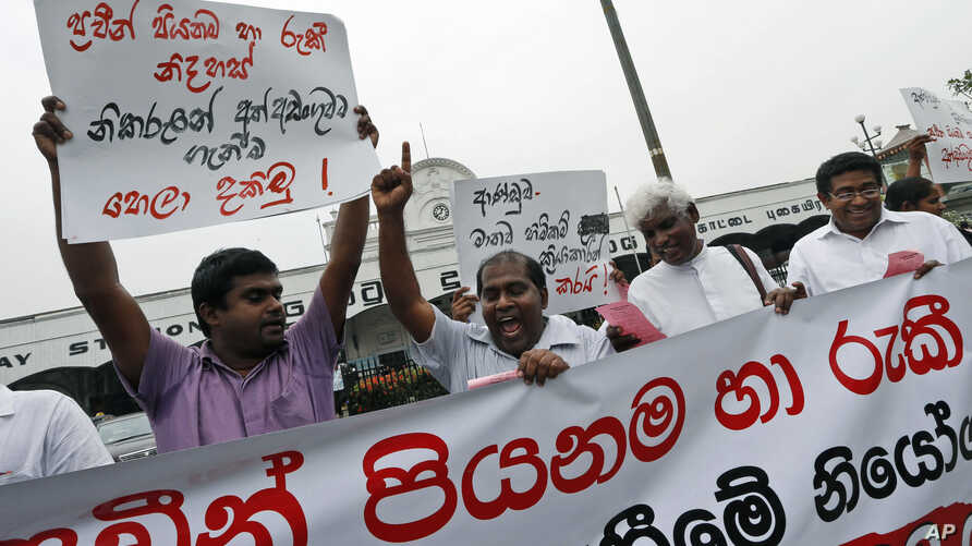 A Sri Lankan human rights activist shouts slogans as others hold a banner and placards against the weekend arrests of right activists in Colombo, Mar. 19, 2014.
