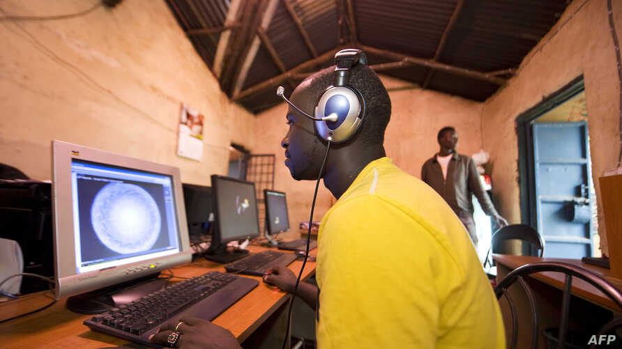 FILE - Young men surf the internet at a cyber cafe on June 20, 2012 in Kibera slum in  Nairobi.
