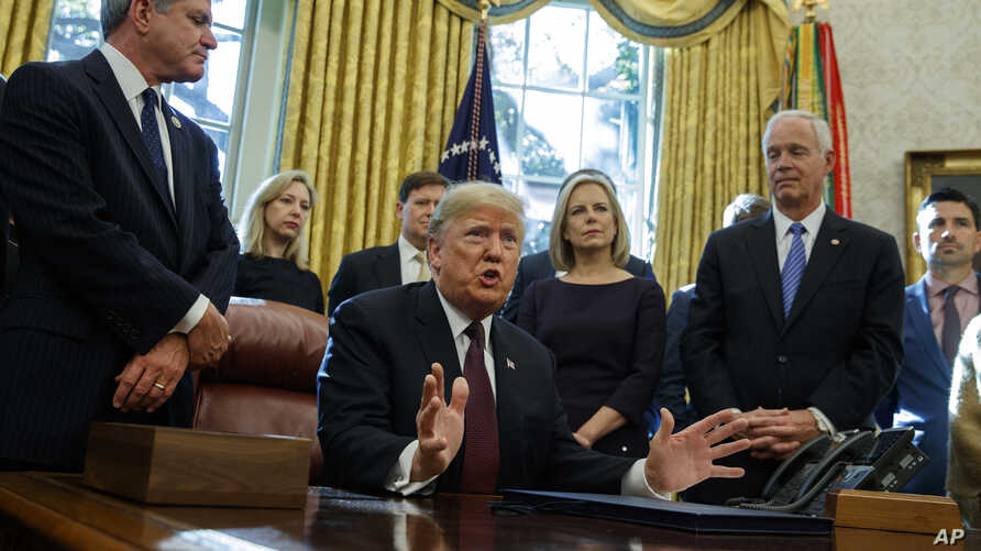 "President Donald Trump answers a reporters question about the investigation of special counsel Robert Mueller during a signing ceremony of the ""Cybersecurity and Infrastructure Security Agency Act,"" in the Oval Office of the White House, Nov. 16, 201"