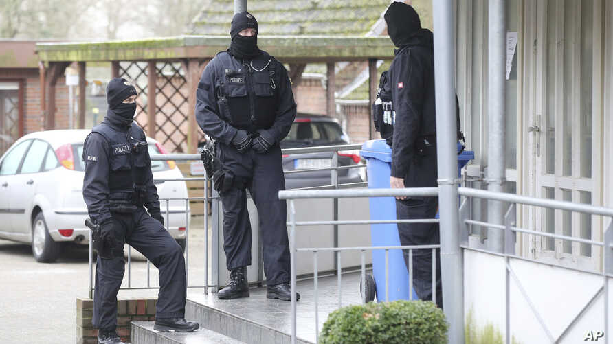 FILE - Police officer stand in front of at building during a raid in the village Meldorf, Germany, Jan. 30, 2019. German authorities arrested three suspected Islamic extremist Iraqi men in the northern German coastal region, on allegations they were