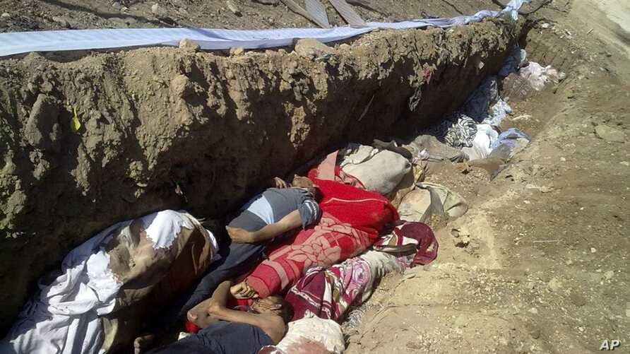 This citizen journalism image provided by Shaam News Network SNN, taken on Sunday, Aug. 26, 2012, purports to show people killed by shabiha, pro-government militiamen, being buried in a mass grave in Daraya, Syria. According to activists' accounts, g