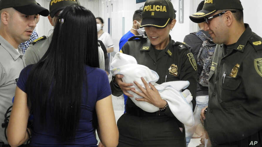 In this June 1, 2018 photo provided by the Colombia National Police, officers arrive to a hospital with an abandoned newborn baby girl who was discovered swaddled by a car near a stadium in Cucuta, Colombia.