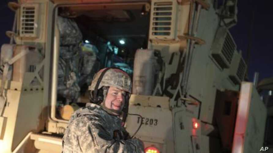 A US Army soldier smiles after crossing into Kuwait as the last convoy pulls out of Iraq, December 18, 2011.