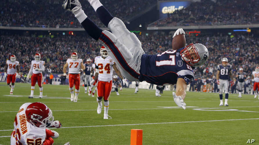 New England Patriots tight end Rob Gronkowski (top) scores a touchdown over Kansas City Chiefs linebacker Derrick Johnson in the second half of their NFL football game in Foxborough, Massachusetts November 21, 2011.   REUTERS/Brian Snyder    (UNITED
