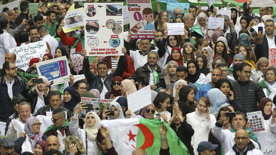 Algerians, many of the medical professionals and students, march with banners and flags during an anti-government protest in Algiers, Algeria, March 19, 2019.
