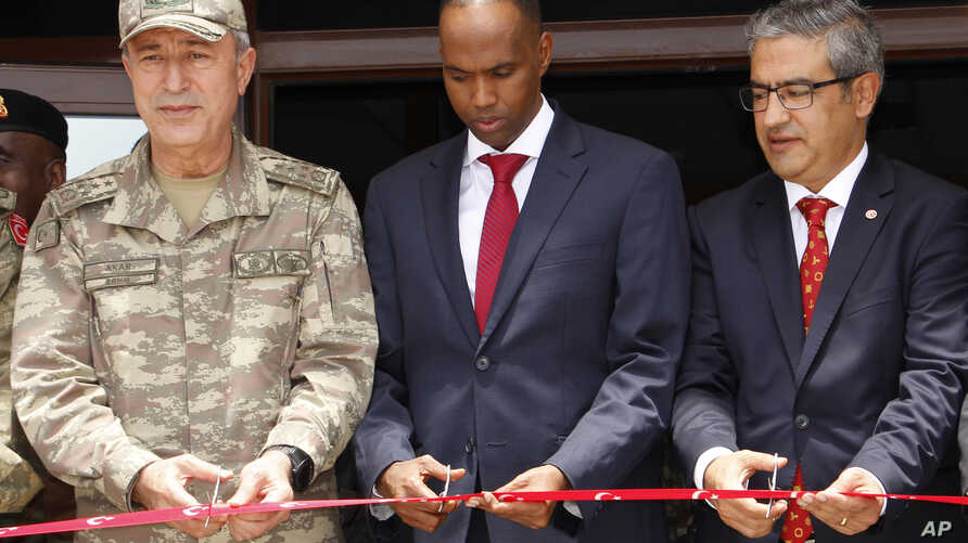 Turkish Chief of Staff General Hulusi Akar, left, Somali prime minister Hassan Ali Khayre, center, and Turkish Ambassador to Somalia Olgan Bekar cut a ribbon to open the  Turkey-Somali military training center in Mogadishu, Sept. 30, 2017.