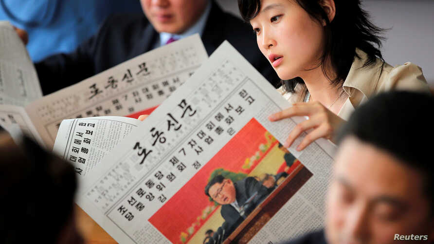 Foreign reporters and their government guides follow, in newspapers and broadcasted on television, the address by North Korean leader Kim Jong Un to the Workers' Party of Korea (WPK) congress, at a hotel in central Pyongyang, North Korea, May 8, 2016...