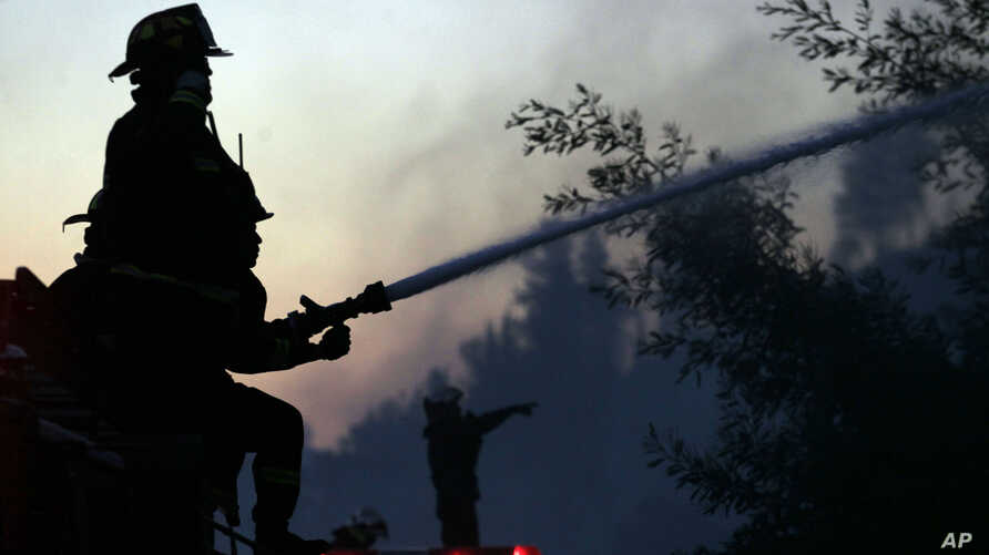 A firefighter sprays water into a burning forest in Valparaiso, Chile, March 14, 2015.