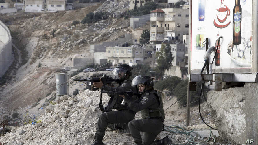 Israeli border policemen aim their weapons during clashes with Palestinian students  in Abu Dis,West Bank, Nov. 2, 2015.