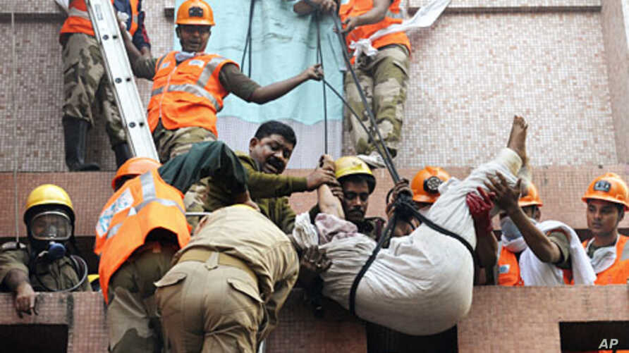 Rescue workers use ropes to evacuate people after a fire broke at a hospital, in Kolkata, India, December 9, 2011.