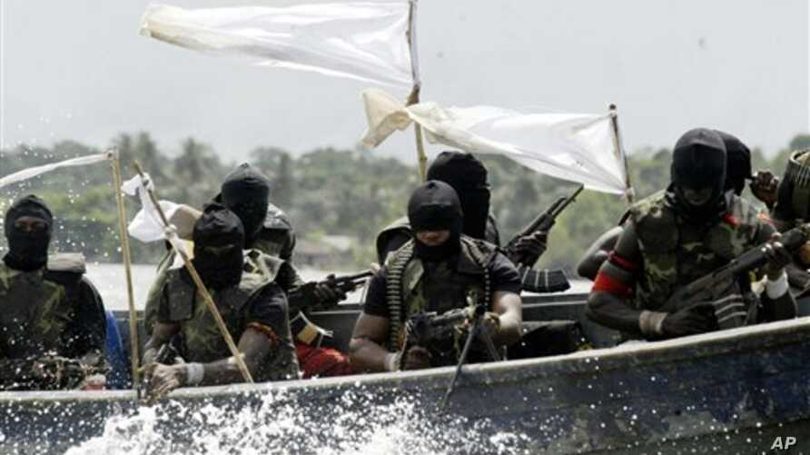FILE - Militants with Kalashnikov assault rifles and rocket-propelled grenade launchers patrol creeks of the Niger Delta, southern Nigeria, Feb. 24, 2006.