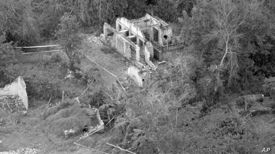 FILE - In this Jan. 8, 1970, file photo, paths marked off with white tape strung between metal stakes relay the remains of homes in My Lai, Vietnam. The paths have been cleared of booby traps so that investigators can move around the hamlet in relati