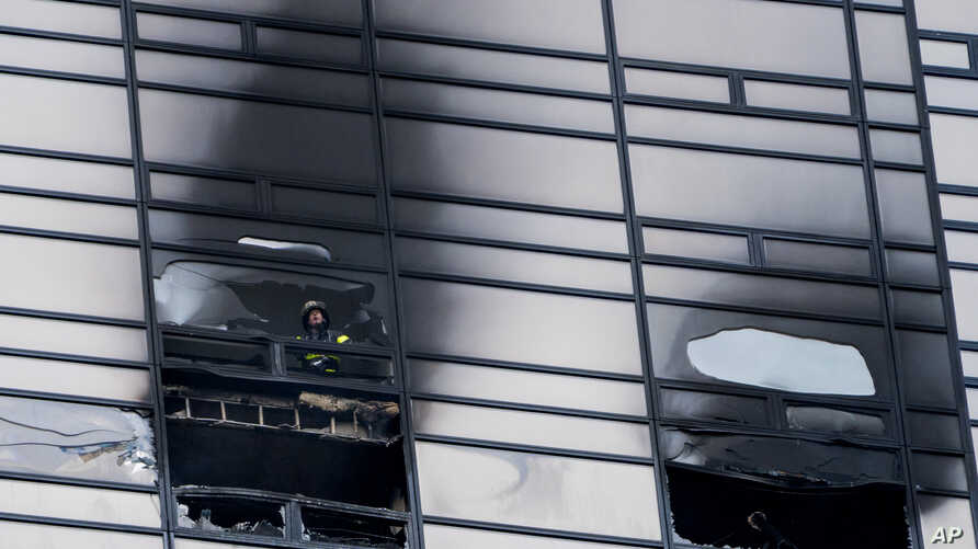 A firefighter looks out from the window of a damaged apartment in Trump Tower, in New York, April 7, 2018.