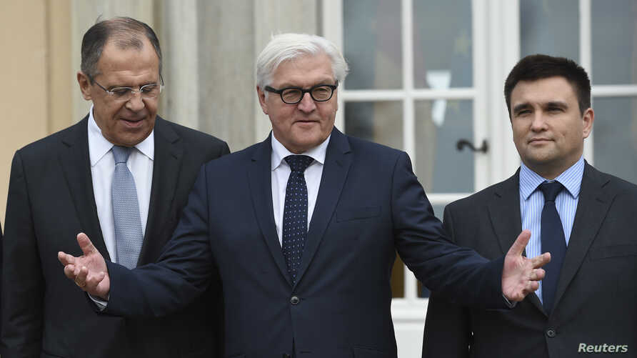 Russian Foreign Minister Sergei Lavrov, German Foreign Minister Frank-Walter Steinmeier and Ukrainian Foreign Minister Pavlo Klimkin (L-R) stand outside German foreign ministry's guest house Villa Borsig near Tegel airport in Berlin, ahead of their m