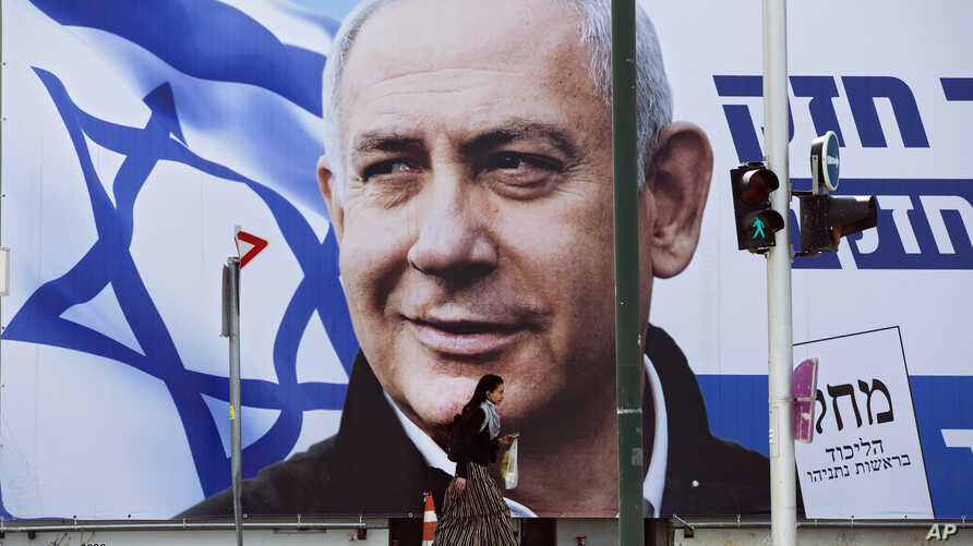 FILE - A woman walks by an election campaign billboard showing Israeli Prime Minister Benjamin Netanyahu in Tel Aviv, Israel, March 28, 2019.