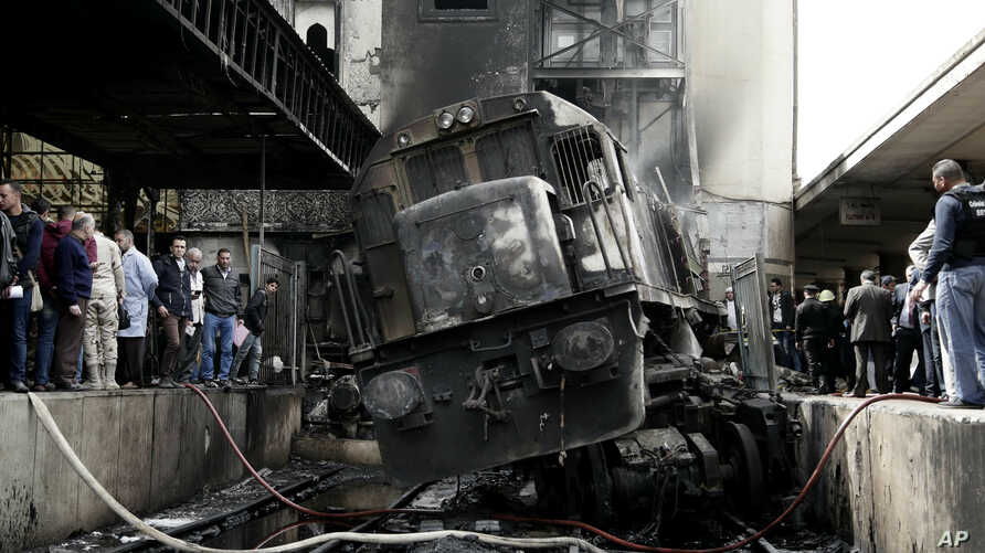 People look at a damaged train inside Ramsis train station in Cairo, Egypt, Wednesday, Feb. 27, 2019. People look at a damaged train inside Ramsis train station in Cairo, Egypt, Wednesday, Feb. 27, 2019. The crash caused an explosion of the locomotiv