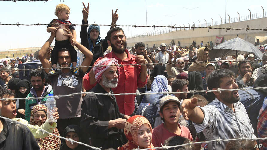 FILE - Syrian refugees gather at the Turkish border as they flee intense fighting in northern Syria between Kurdish fighters and Islamic State militants in Akcakale, southeastern Turkey, June 15, 2015.