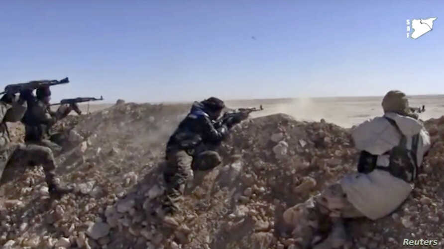 This photo from a video provided by the Syria Democratic Forces (SDF), shows fighters from the SDF opening fire on an Islamic State group's position, in Raqqa's eastern countryside, Syria, March 6, 2017.