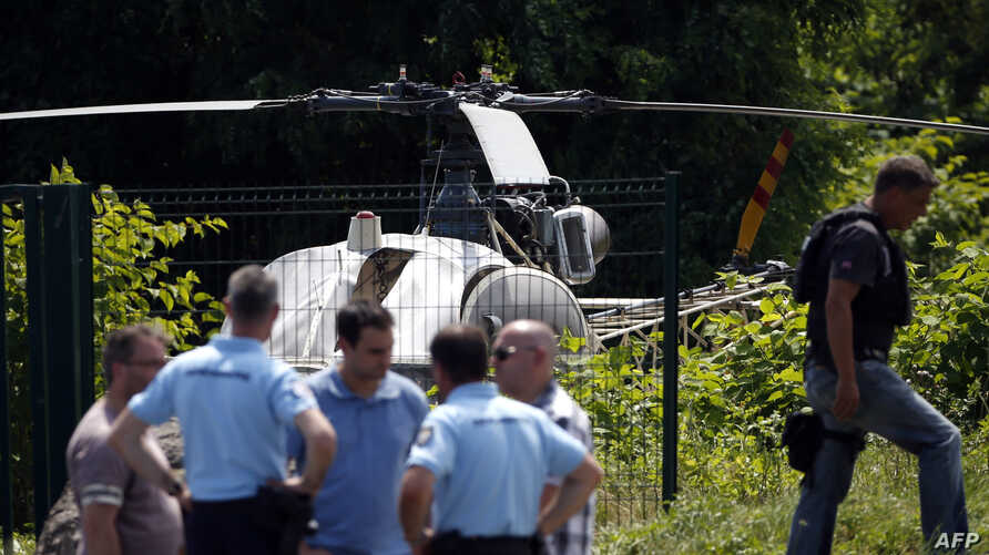 This picture taken July 1, 2018, in Gonesse, north of Paris, shows police near a helicopter abandoned by notorious French gangster Redoine Faid after his escape from prison in Reau, France.