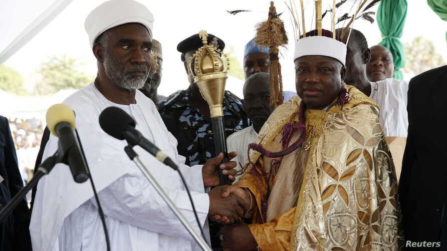 Kwire-Mana, Kpafrato II, Homun Honest Stephen (R), receives his staff of office from Adamawa State Governor, Murtala Nyako, during a presentation ceremony at Makwada Square in Numan, Adamawa state, December 7, 2013. The ceremony was held to confer Ho