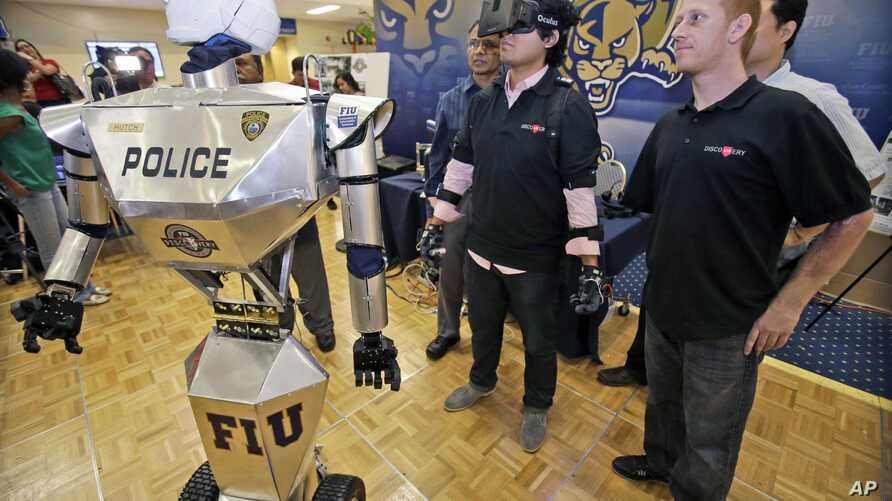 """FILE - Students control a """"Robocop"""" during a demonstration at Florida International University, Feb. 12, 2014, in Miami."""