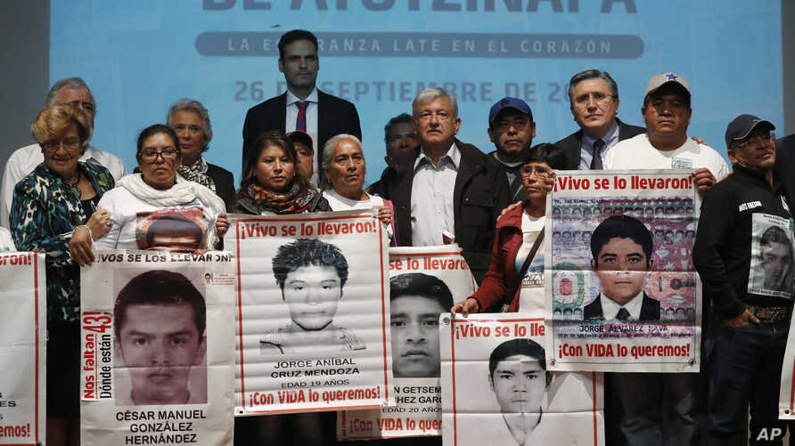 President-elect Andres Manuel Lopez Obrador, center, poses with the relatives of some the 43 college students who disappeared on Sept. 26, 2014, at the Memory and Tolerance Museum in Mexico City, Sept. 26, 2018.