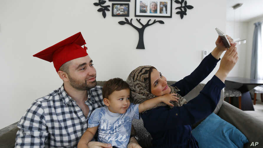 Mohamad Bassel Khair, left, holds his son, Sami Kahir, 2, as his wife Lama Alassil takes a photo of them to post on the Snapchat application during a photo session with The Associated Press in his home in Clifton, N.J. Khair, of Damascus, Syria, is g