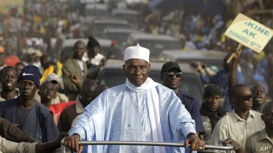 Senegalese President Abdoulaye Wade is surrounded by supporters and security as he travels between campaign stops in downtrodden suburban neighborhoods of Dakar, Senegal Wednesday, Feb. 22, 2012.