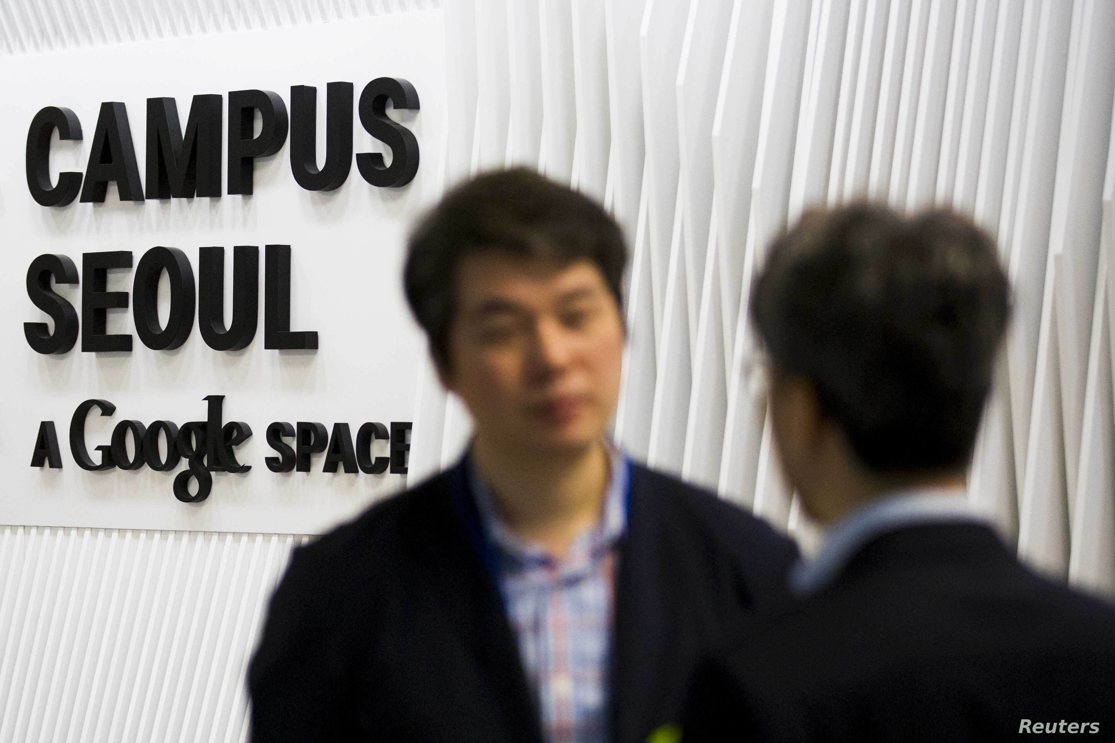 People talk at the entrance to the Google Campus start-up space in the Gangnam district of Seoul, May 8, 2015.