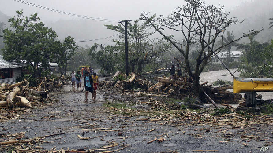 FILE - People walk through debris in Samoa's capital Apia, Dec. 14, 2012, after cyclone Evan ripped through the South Pacific island nation.