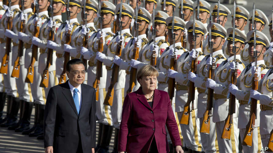 Chinese Premier Li Keqiang, left walks with  German Chancellor Angela Merkel during a welcome ceremony held outside the Great Hall of the People in Beijing, China, Thursday, Oct. 29, 2015.