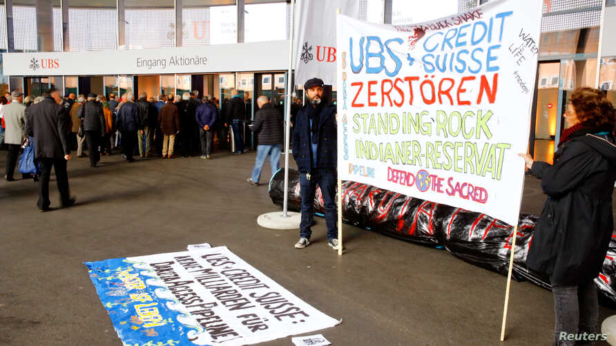 Protesters display a banner to protest against the financing of the Dakota Access oil pipeline by Swiss banks UBS and Credit Suisse as participants arrive ahead of the annual shareholder meeting of Swiss bank UBS in Basel, Switzerland May 4, 2017. Th